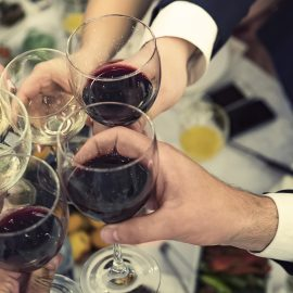 Top-down view of male and female hands with filled glasses of wine above the restaurant tabletop. Drinking toasts and clinking tumblers at a dinner party. Drinking wine at a banquet. Feast an event